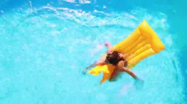 Overhead of brunette sitting on lilo in pool on sunny day — Stock Video