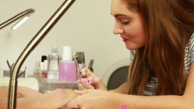 Nail technician applying nail varnish to customers nails — Vídeo Stock
