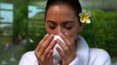 Beautiful brunette in bathrobe drinking herbal tea at the spa — Stock Video