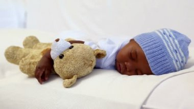 Boy sleeping in crib with teddy bear — Video Stock