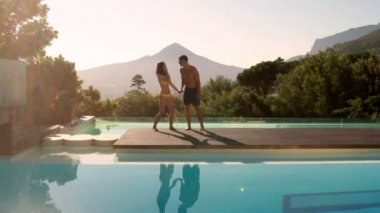 Happy couple leaping into the outdoor swimming pool — Stock Video
