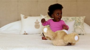 Baby girl playing with teddy bear — Vídeo de stock