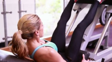 Woman using leg weights machine — Stockvideo