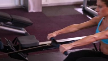 Fit woman using rowing machine — Stock Video