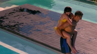 Man giving his pretty girlfriend a piggy back poolside — Stockvideo