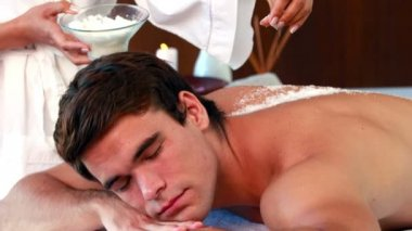 Handsome man getting a salt scrub treatment — ストックビデオ