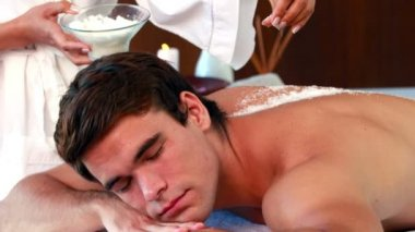 Handsome man getting a salt scrub treatment — Vídeo de stock