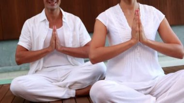 Smiling couple in white sitting in lotus pose with hands together — Vidéo