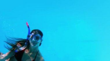 Pretty brunette swimming underwater into pool with snorkel — Stock Video