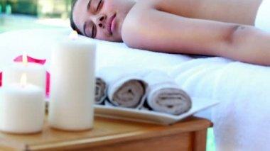 Calm brunette getting hot stone massage poolside — Stock Video