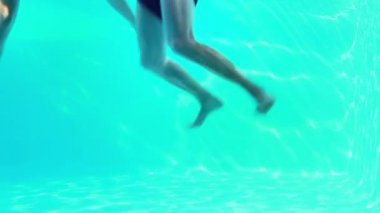 Happy couple jumping in swimming pool waving at camera — Vidéo