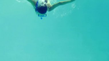Pretty brunette diving into swimming pool wearing snorkel — Stock Video