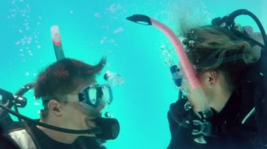 Couple in scuba gear looking at each other underwater — Stock Video