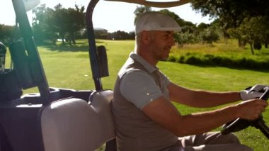 Happy golfer driving buggy on the golf course — Stok video