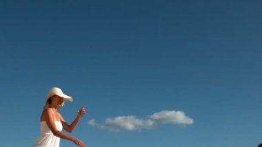 Smiling blonde running and taking off her sunhat — Stock Video