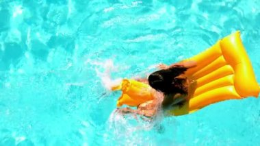 Brunette splashing on lilo in the swimming pool — Stock Video