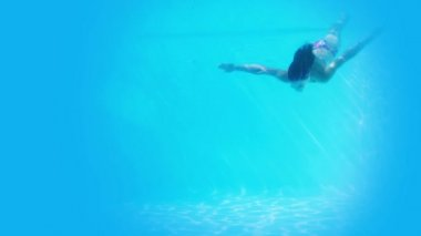 Pretty brunette swimming underwater in pool — Stock Video