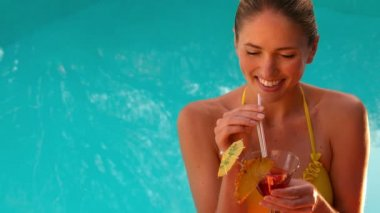 Sexy blonde drinking cocktail in yellow bikini poolside — Vídeo de stock
