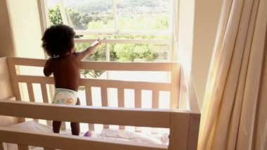 Baby in her crib looking out window — Stock Video