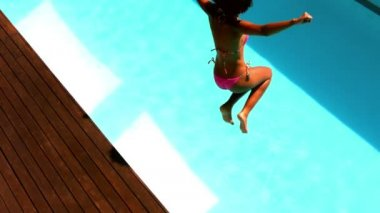 Woman in pink bikini jumping into swimming pool — Stock Video