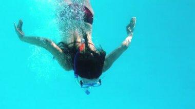 Brunette swimming underwater wearing snorkel — Stock Video