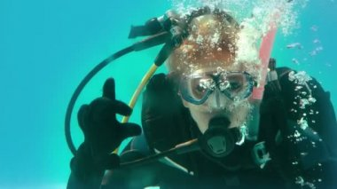 Woman in scuba gear looking at camera underwater — Stock Video