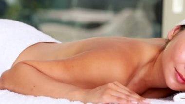 Beautiful brunette lying on massage table with eyes closed — 图库视频影像