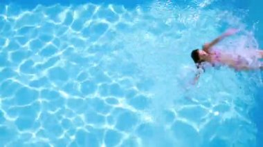Overhead of brunette swimming in pool on sunny day — Vídeo de stock