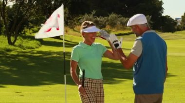 Couple on the putting green high fiving — Stockvideo