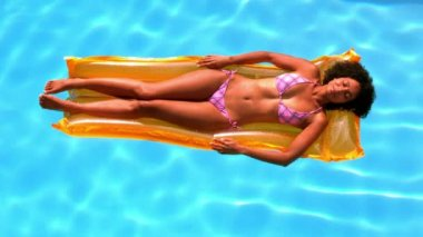 Happy woman relaxing on lilo in swimming pool — Stock Video