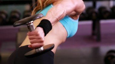 Fit woman lifting dumbbells — Wideo stockowe