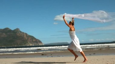 Carefree blonde running on the beach holding scarf up — Stockvideo