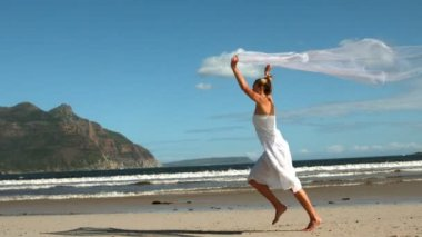 Carefree blonde running on the beach holding scarf up — Stok video
