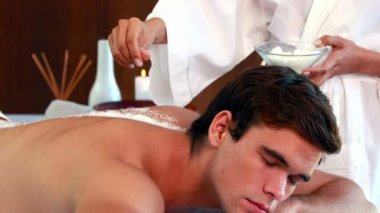 Handsome man getting a salt scrub treatment — Stockvideo