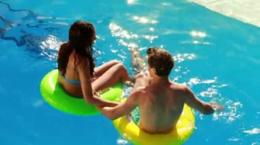 Couple sitting on inflatable rings in the swimming pool — Vídeo de stock