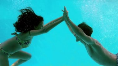 Couple holding hands underwater in swimming pool — Stock Video