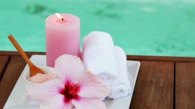 Towels candles and pink flower by the pool — Vídeo Stock