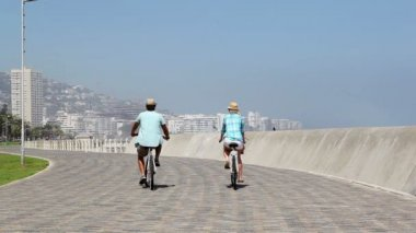 Couple going for a bike ride by seaside — Wideo stockowe