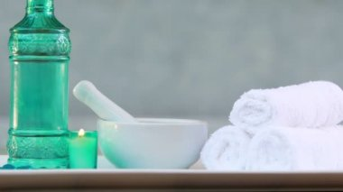 Towels and glass bottle with candle and mortar and pestle — Stock Video