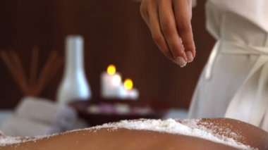 Beauty therapist pouring salt scrub on back — Stock Video