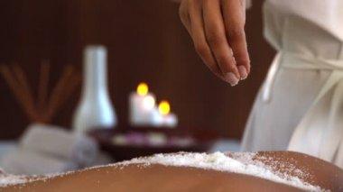 Beauty therapist pouring salt scrub on back — Stock Video