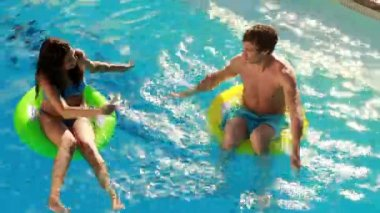 Couple sitting on inflatable rings in the swimming pool — Stock Video
