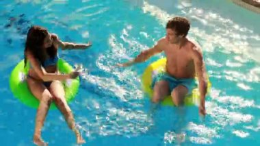 Couple sitting on inflatable rings in the swimming pool — 图库视频影像