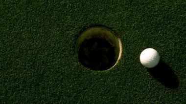 Golf ball rolling into the hole on putting green — Stockvideo