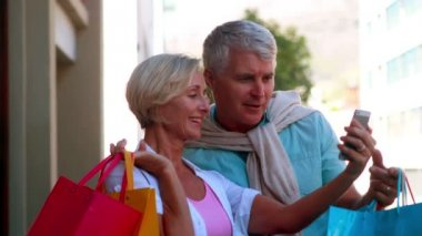 Couple shopping looking at smartphone — Vídeo de stock