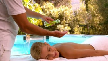 Masseuse pouring oil onto hands for massage — Stock Video