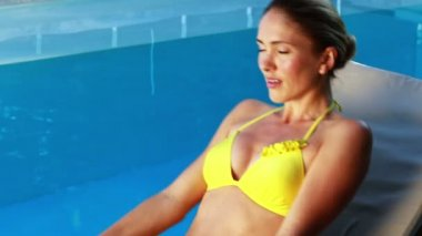 Gorgeous blonde in bikini enjoying the sunshine poolside — Stock Video