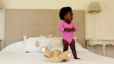 Girl playing and clapping on bed — Vídeo de stock