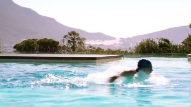 Fit swimmer doing butterfly stroke in outdoor pool — Wideo stockowe
