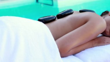 Peaceful brunette getting hot stone massage poolside — Stock Video
